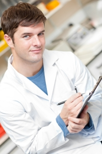 Handsome scientist holding a clipboard and smiling at the camera in his laboratory